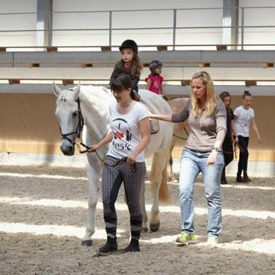 Das Bild zeigt ein kleines Mädchen auf einem weißen Pferd in einer Reithalle. Zwei Frauen finden sich an der Seite des Pferdes.