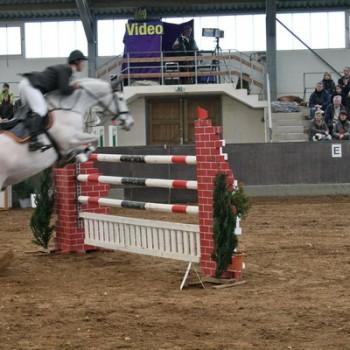 Ein Foto von einem Reiter auf einem weißen Pferd beim Springen über eine Hürde in einer Reithalle.