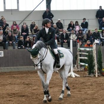 Ein Foto von einem Mann auf einem weißen Pferd in einer Reithalle. Im Hintergrund sind Zuschauer zu erkennen.