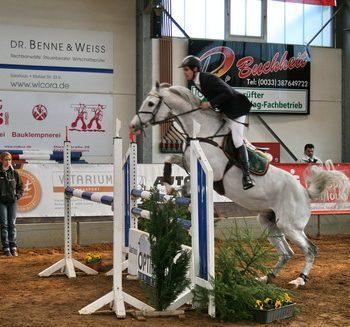 Ein Reiter auf einem weißen Pferd beim Springen über eine Hürde in einer Reithalle.