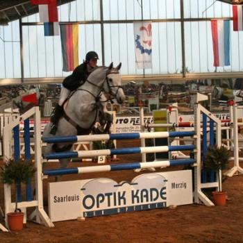 Ein Foto von einer Reiterin auf einem weißen Pferd beim Springen über eine Hürde in einer Reithalle.